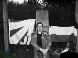 [Foto: Christoph Schmidt vorm Gedenkstein an der Restfläche des KZ-Außenlagers Witten Annen mit JN- und Reichsflagge]